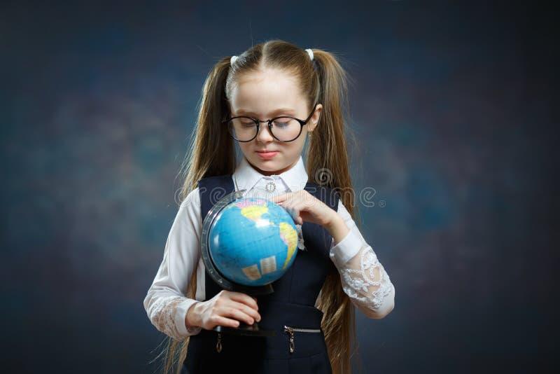 Les verres caucasiens d'usage d'écolière tournent le globe du monde image libre de droits