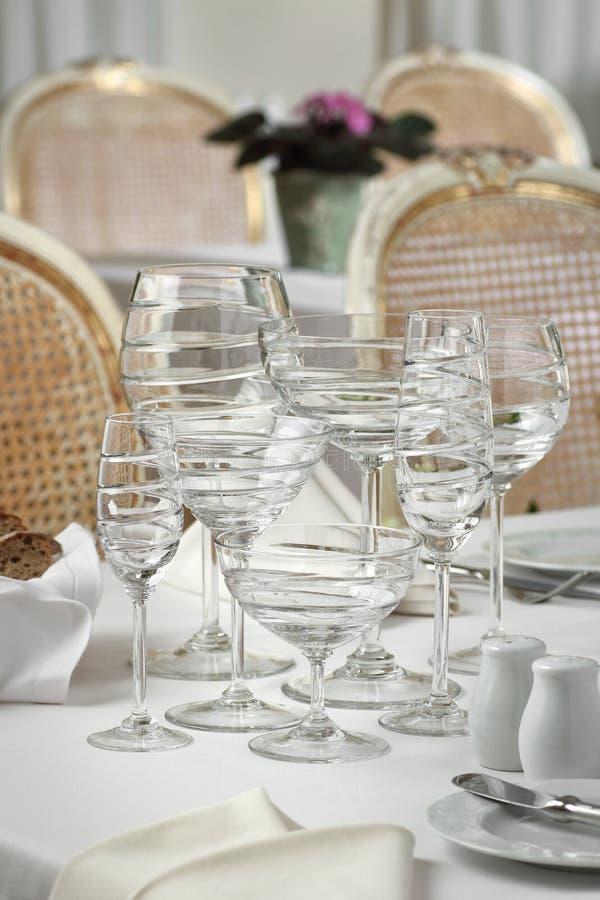 Les verres cristal sur la table dans le restaurant ajournent l'arrangement photo libre de droits