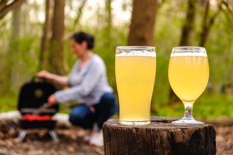 Les verres de bière avec le poulet rôti de femme s'envole sur le barbecue de gril à l'arrière-plan image stock
