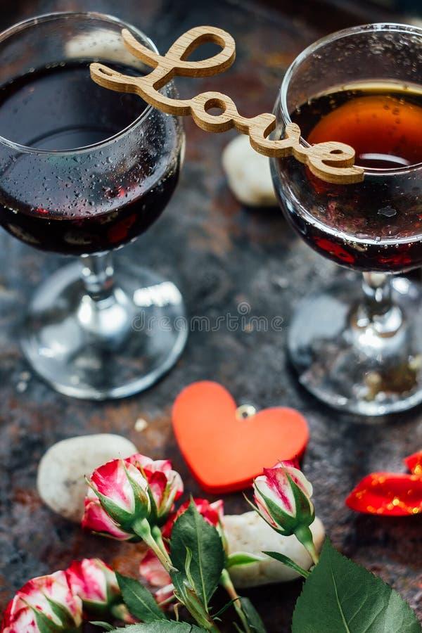 Les verres de la Saint-Valentin wine avec les lettres AIMENT, des fleurs et des coeurs photographie stock