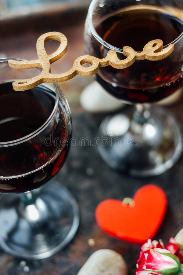 Les verres de la Saint-Valentin wine avec les lettres AIMENT, des fleurs et des coeurs image stock