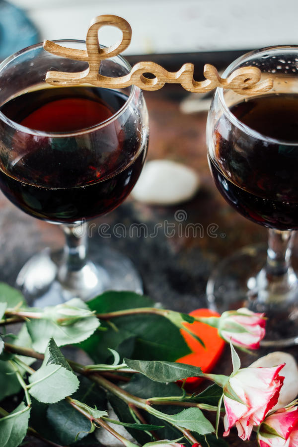 Les verres de la Saint-Valentin wine avec les lettres AIMENT, des fleurs et des coeurs photos stock