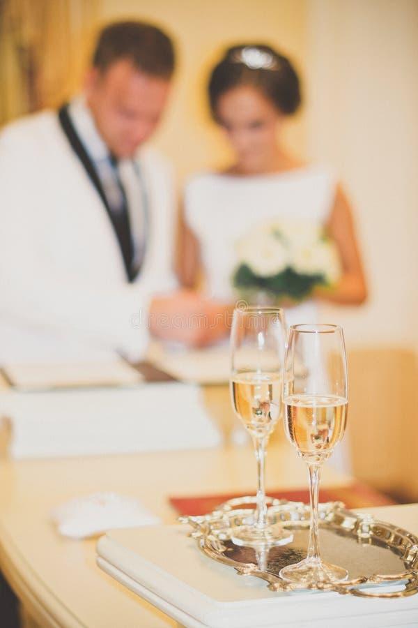Les verres de mariage sont dans le premier plan Nouveaux mariés brouillés d'ensembles photo libre de droits