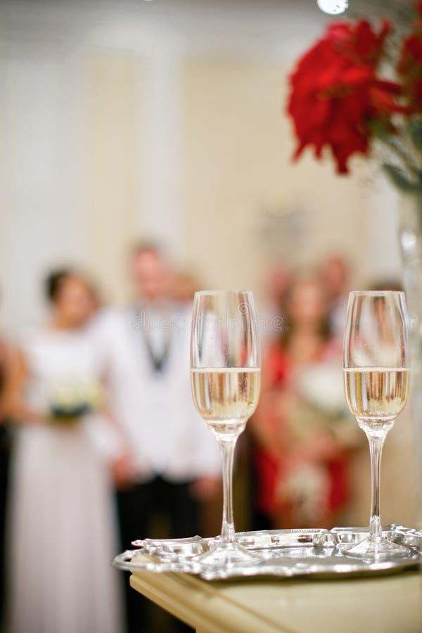 Les verres de mariage sont dans le premier plan Nouveaux mariés brouillés d'ensembles photo stock