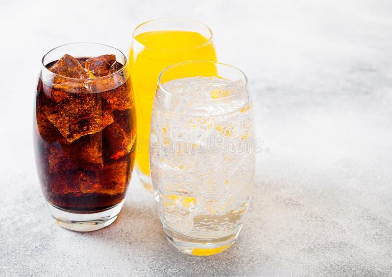 Les verres de soude boivent avec des glaçons et des bulles sur le fond en pierre de table de cuisine Kola et soude orange de limo image stock
