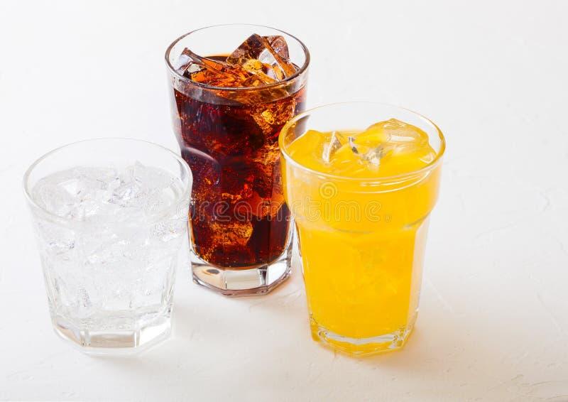 Les verres de soude boivent avec des glaçons et des bulles sur le fond en pierre de table de cuisine Kola et soude orange de limo photo libre de droits