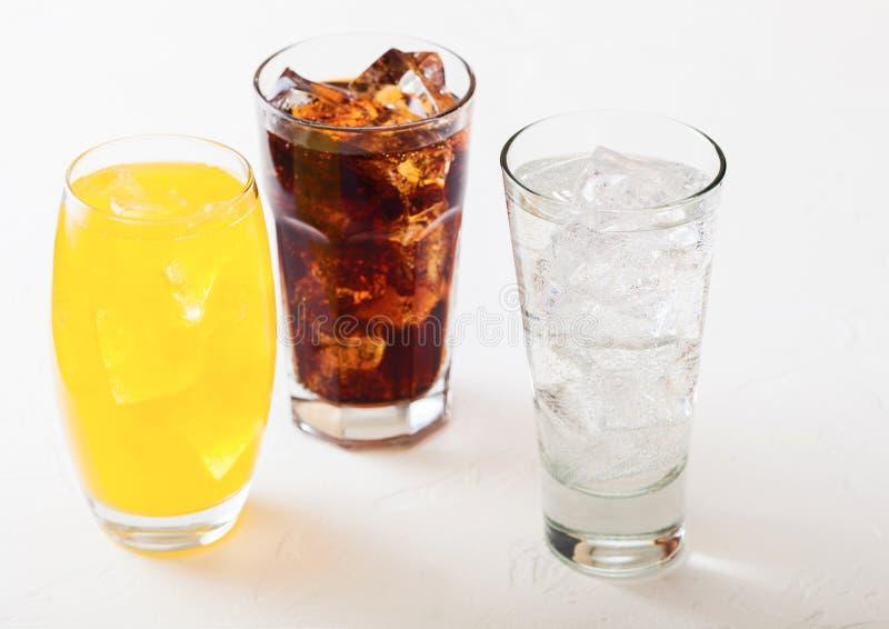 Les verres de soude boivent avec des glaçons et des bulles sur le fond en pierre de table de cuisine Kola et soude orange de limo photos libres de droits
