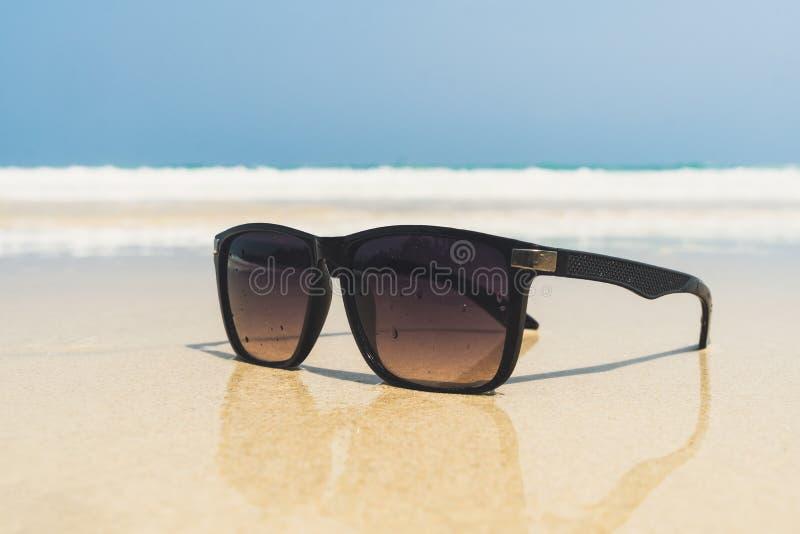 Les verres de Sun se trouvent sur une plage près de la mer photographie stock libre de droits
