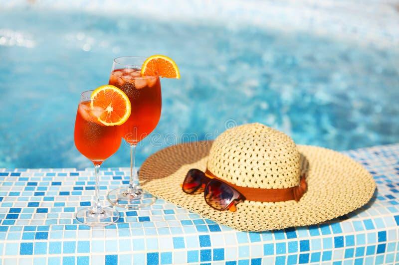 Les verres du cocktail orange d'alcool sur la turquoise arrosent le fond images libres de droits