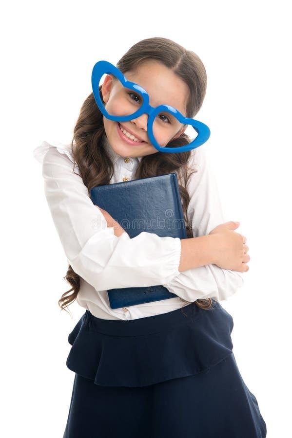 Les verres en forme de coeur d'écolière ont isolé le fond blanc L'uniforme scolaire de fille d'enfant vêtx le livre d'étreintes U photographie stock