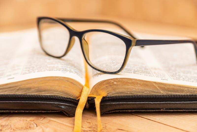 Les verres pour le mensonge de vue sur la bible, la bible dans la couverture noire en cuir avec des étiquettes se trouve sur la t photos libres de droits