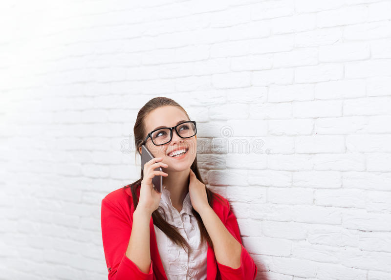 Les verres rouges de veste de sourire de femme d'affaires de téléphone portable d'appel téléphonique d'usage heureux de problème  photos libres de droits