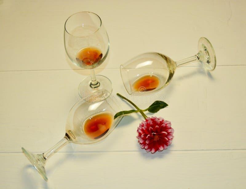 Les verres transparents se trouvent avec le vin rouge sur un fond blanc image libre de droits