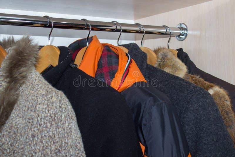 Les vestes d'hiver dans la garde-robe, accrochant l'hiver de cintres vêtx du cabinet de garde-robe images libres de droits