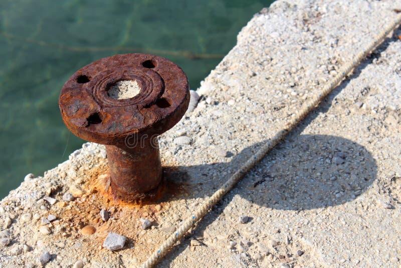 Les vieilles bornes rouillées d'amarrage de fer ont monté sur le pilier concret images stock