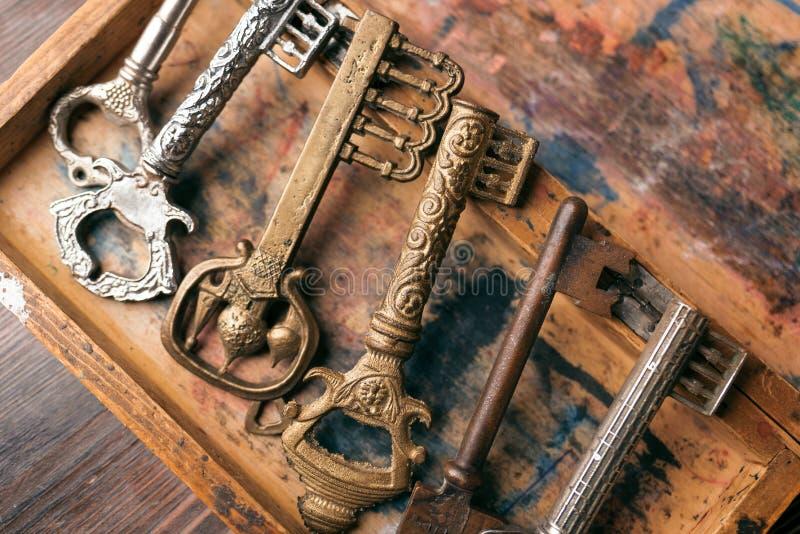 Les vieilles clés découpées sur un vintage embarquent avec une peinture minable photos libres de droits