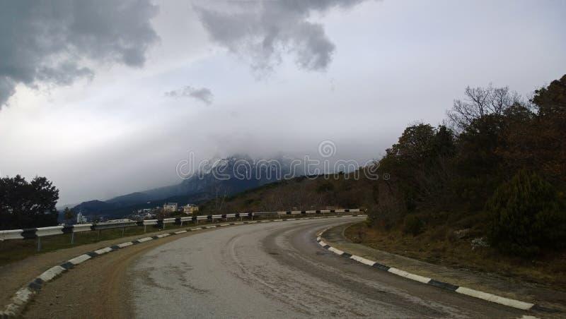 Les vieilles courbes de route dans les montagnes Voie dangereuse par temps nuageux brumeux photographie stock libre de droits
