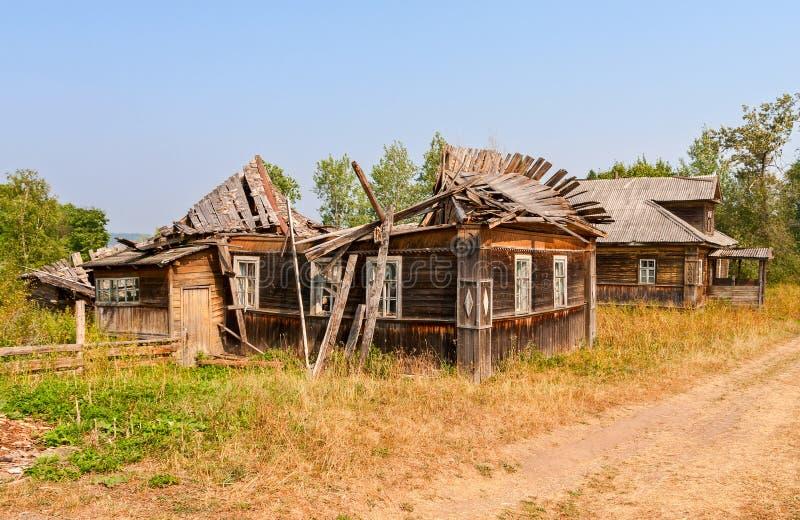 Les vieilles maisons cassées en bois dans le Russe ont abandonné le village photographie stock libre de droits