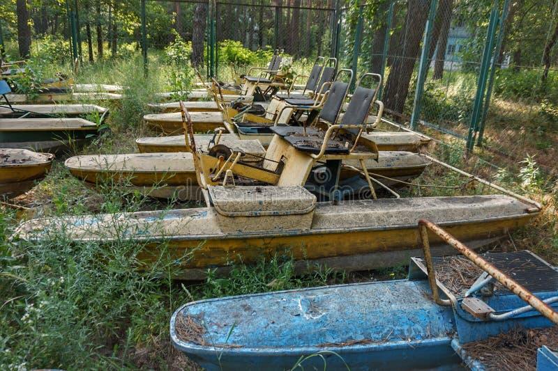 Les vieux bateaux et catamarans ont traîné à terre Rouille sur le pré parmi l'herbe photos stock