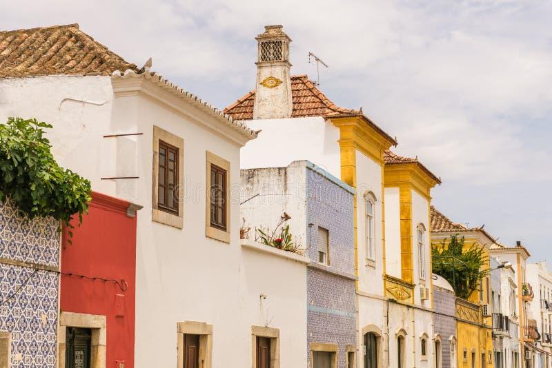 Les vieux, colorés bâtiments avec l'équilibre fleuri et les tuiles rayent une rue photos stock