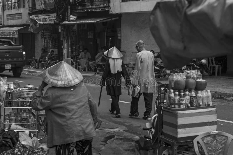 Les vieux couples dans des vêtements traditionnels descendent une rue et un vendeur féminin contrôle sa stalle dans une rue de Ho images libres de droits