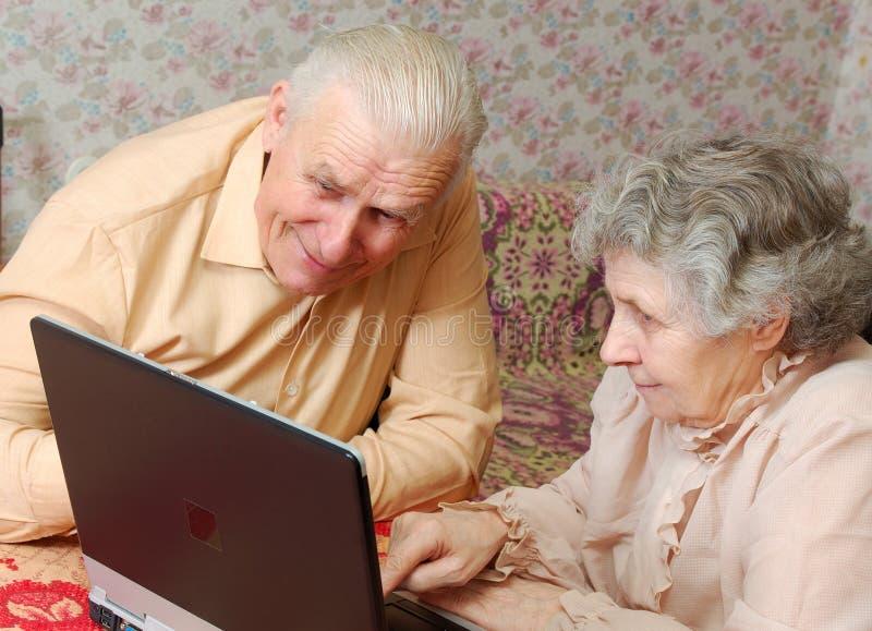 Les vieux couples regardent à l'ordinateur portatif avec l'intérêt actif photos libres de droits