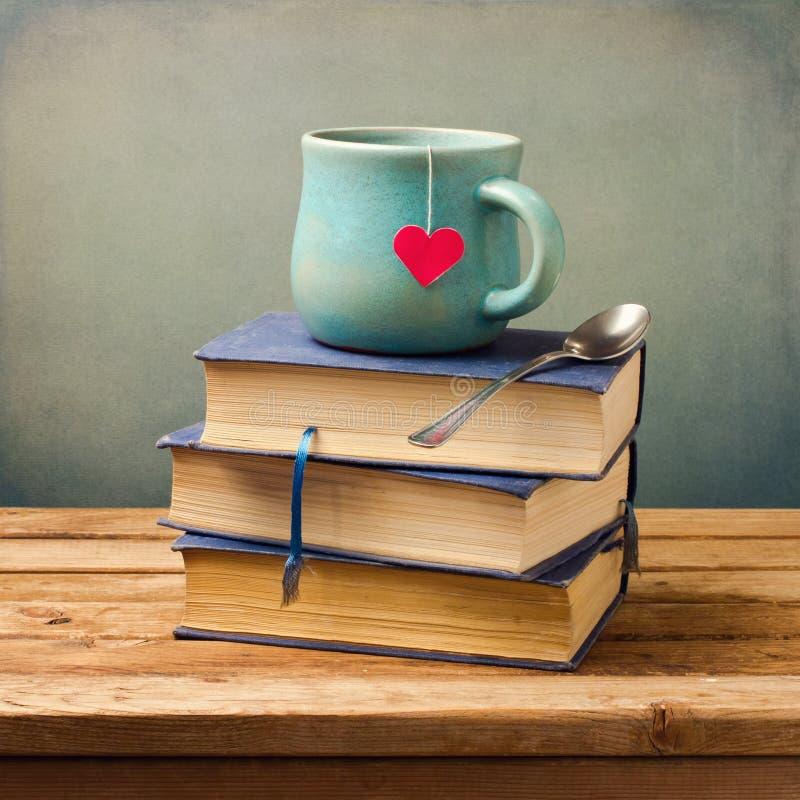 Les vieux livres et cuvette de cru avec le coeur forment image libre de droits