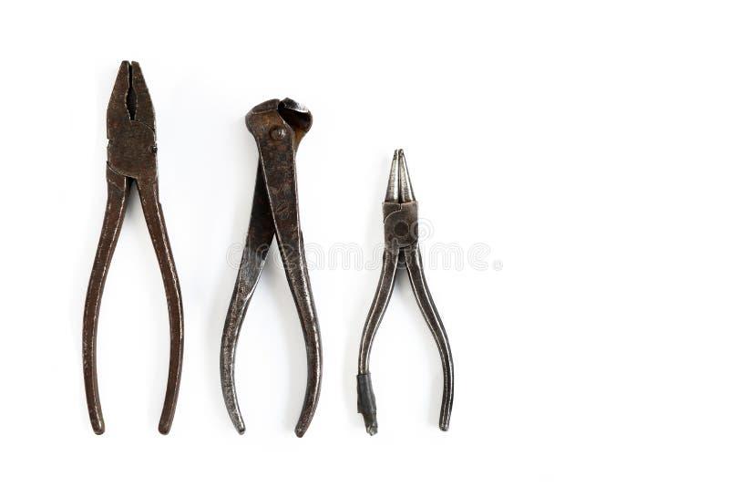 Les vieux outils se trouvent sur un fond d'isolement blanc Burins, coupe-fil, pinces, pinces et d'autres outils images stock