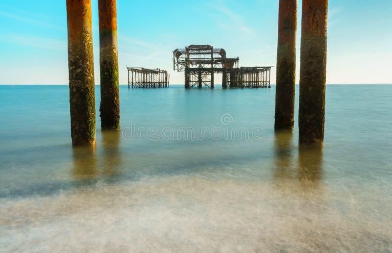 Les vieux restes de Brighton Pier ont laissé la position en mer avec de belles vagues à Brighton et pilier occidental de Hove Tar photos libres de droits
