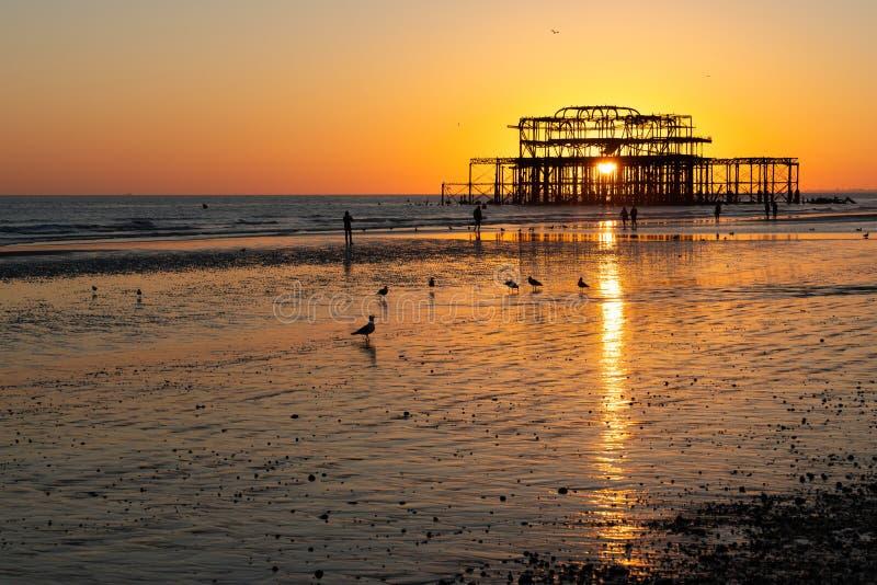 Les vieux restes de Brighton Pier ont laissé la position en mer avec de belles vagues et mouettes sur la plage photos stock