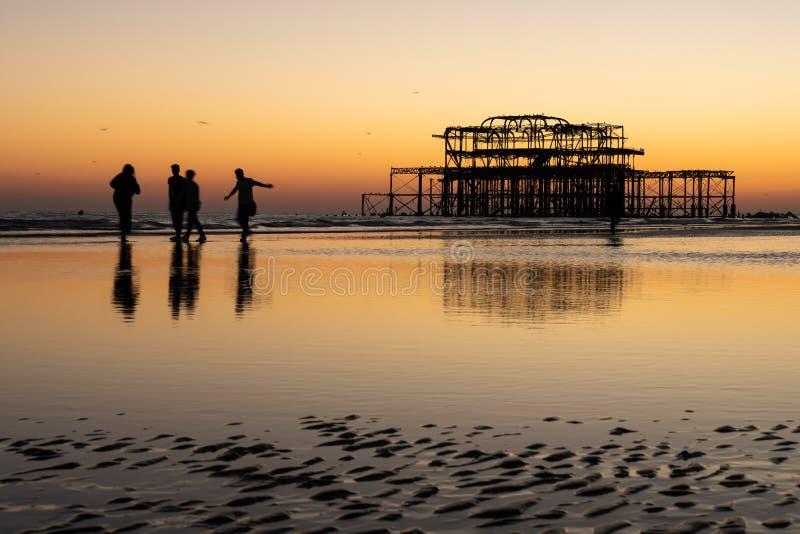 Les vieux restes de Brighton Pier ont laissé la position en mer avec de belles vagues, mouettes et personnes locales sur la plage photos libres de droits