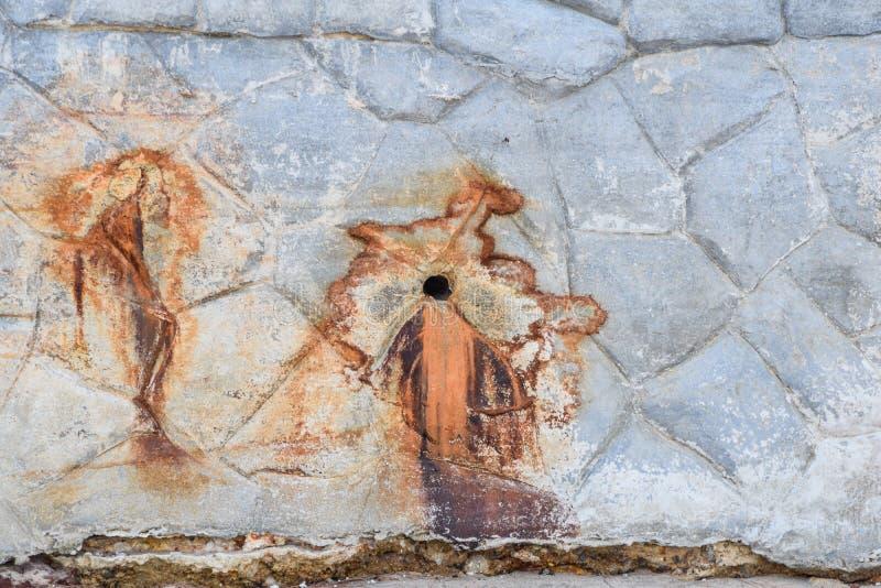 Les vieux trous endommagés de tuyau causent la rouille sur le mur en pierre photographie stock