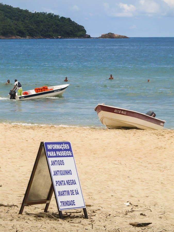 Les visites de offre de bateau de signe aux plages tout près au Praia font Sono, plage populaire dans Paraty, Rio de Janeiro image stock