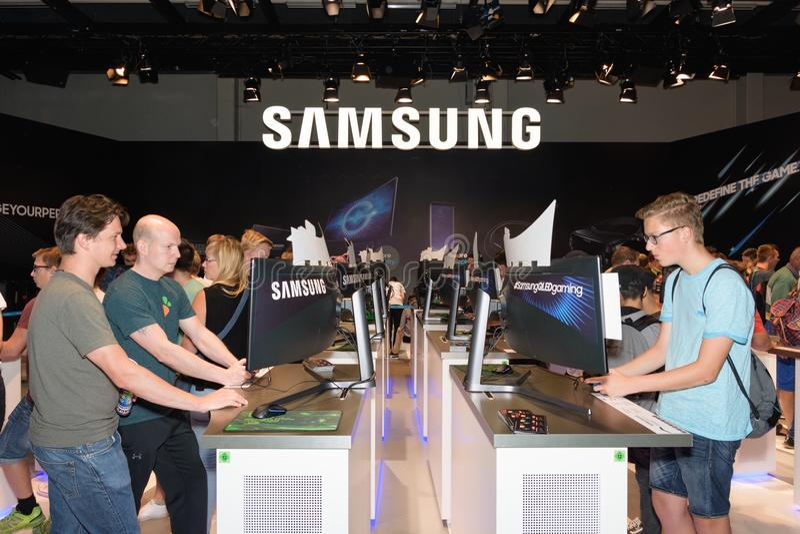 Les visiteurs de foire commerciale jouent et examinent des jeux d'ordinateur à la cabine de photographie stock