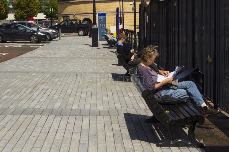 Les visiteurs s'asseyent et détendent sur des bancs donnant sur la rivière Lagan au quartier des docks reconstruit par s de ` de  photographie stock