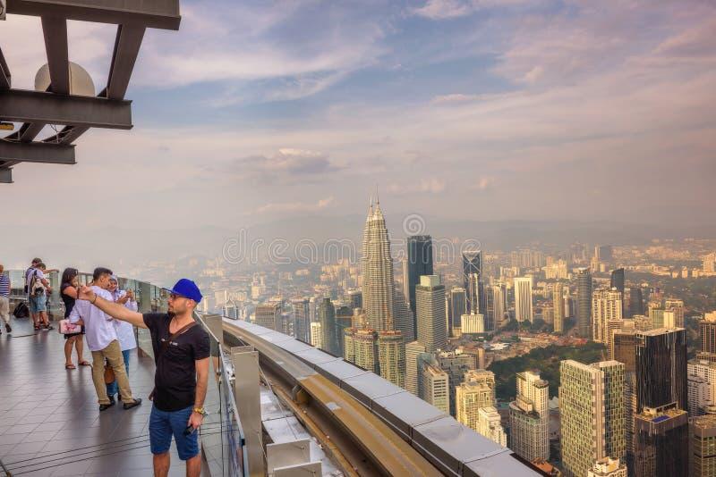 Les visiteurs sur le Menara kilolitre dominent avec la vue de l'horizon de Kuala Lumpur image stock