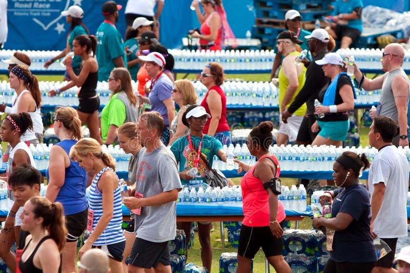 Les volontaires distribuent des bouteilles d'eau aux coureurs épuisés après course images libres de droits