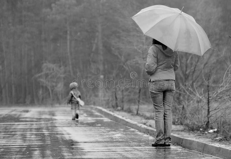 Les wathces de mère en tant que son fils part photographie stock