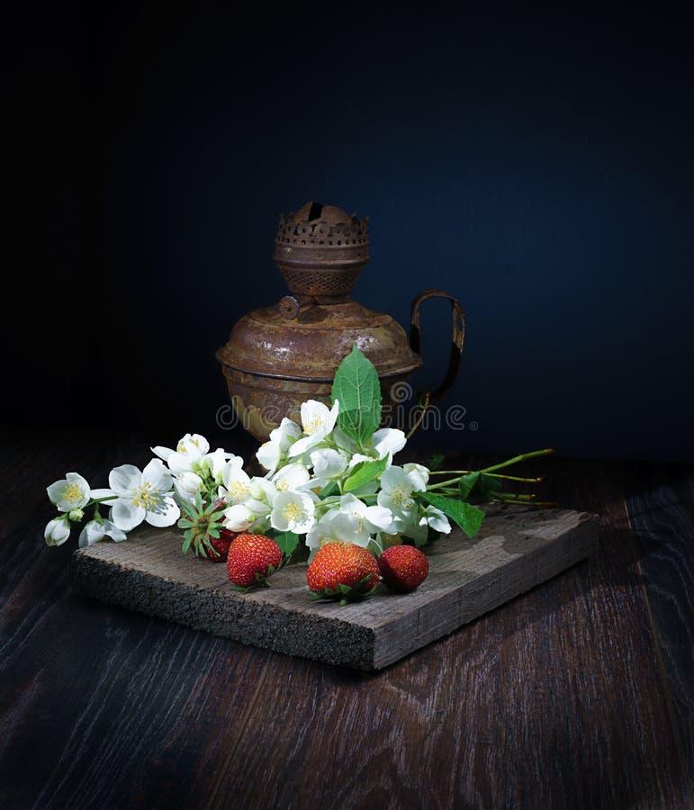 Les wildflowers blancs frais, fraises fraîches, toutes ceci se trouve sur un vrai panneau de bois, et derrière eux il y a une vie photos libres de droits