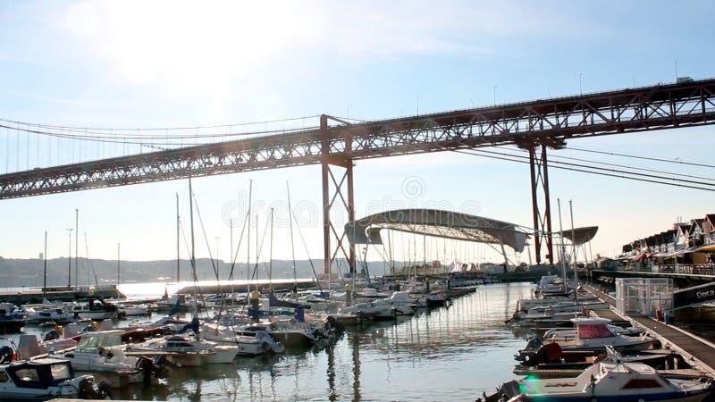 Les yachts ont amarré à la marina sous le pont au coucher du soleil i image libre de droits