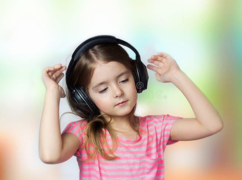Les yeux fermés par fille d'enfant écoutent des écouteurs de musique image stock