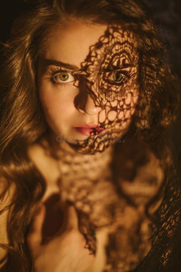 Les yeux passionnés jettent un coup d'oeil Portrait expressif émotif d'une belle fille avec des ombres de dentelle sur son visage photos libres de droits