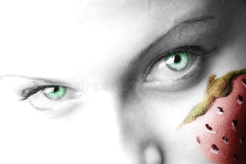 Les yeux verts et la fraise image stock