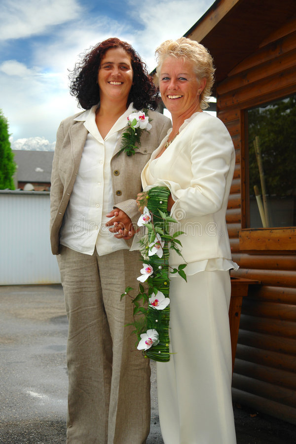 Lesbian brides. Mature lesbian couple posing and holding hands in ceremonial formal dress with bouquet after the official wedding ceremony stock photos