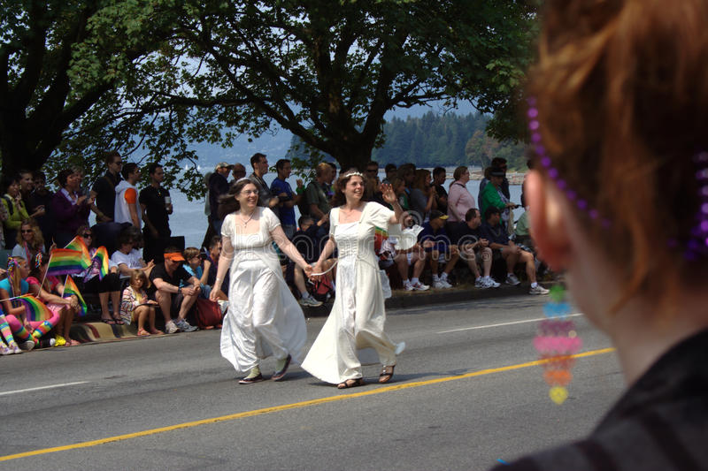 Lesbian Brides, Vancouver Gay Pride Parade. Lesbian brides walk hand-in-hand in the Vancouver Pride Parade. This is a highly politicized statement as same sex royalty free stock photography