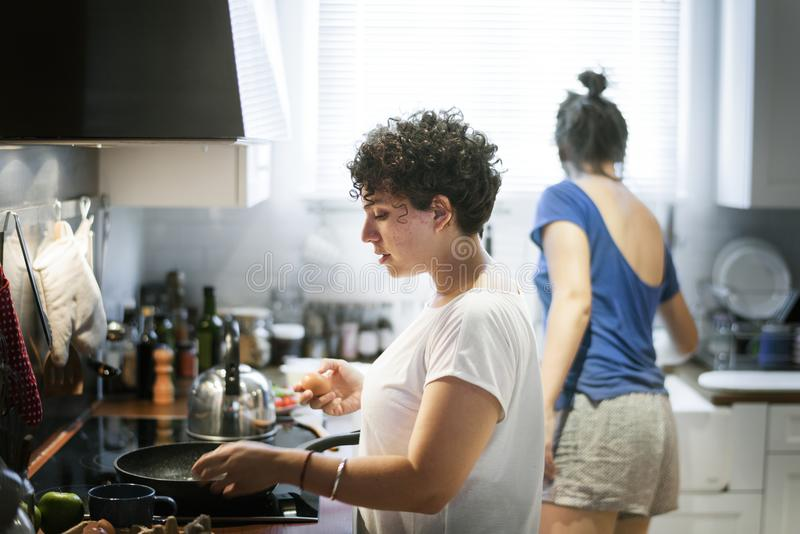 Lesbian couple cooking in the kitchen together royalty free stock image