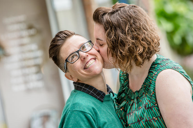 Lesbian couple kissing outdoors stock photos