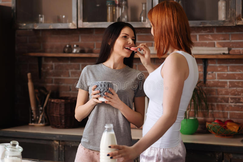 Lesbian couple posing in pajamas at home. Cozy morning. Positive delighted women holding bottle of milk in left hand looking at her girlfriend while putting pink royalty free stock photography