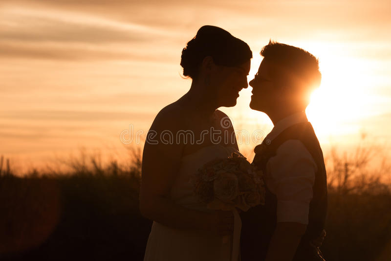 Lesbian Couple at Sunset. Beautiful same sex couple in civil union at sunset royalty free stock photos