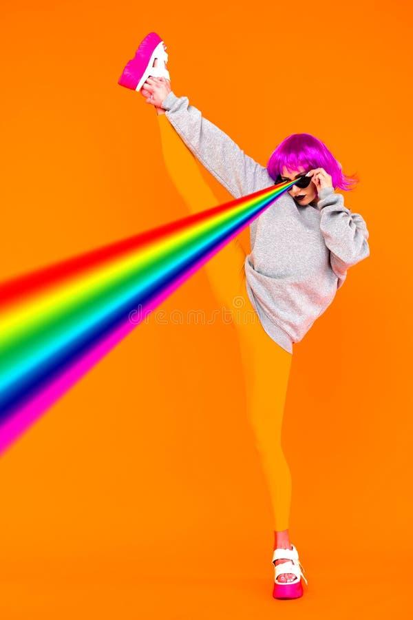 Lesbian dziewczyna w różowej peruce i okularów przeciwsłonecznych krótkopędy stoi na pomarańczowym tle od jej oko tęczy laserów,  zdjęcia stock